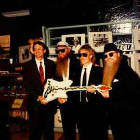 """ZZ Top donates the custom """"Muddywood"""" guitar to Sid Graves at the Carnegie Public Library."""