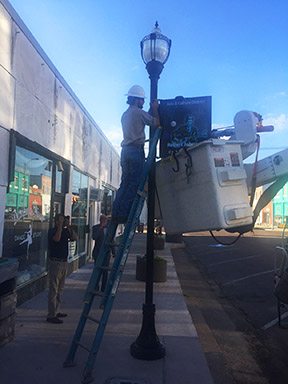 First sign prototype of Robert Johnson being hung by Clarkdale Public Utilities (photo by Richard Bolen).
