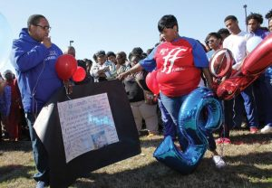 Lekitha Hill, mother of Dayeveon Hill, looks at a handmade poster in memory of her son.